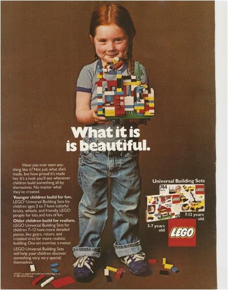 Une petite fille en jeans et baskets, debout, face au spectateur présente la construction qu'elle a réalisée avec des briques Lego.