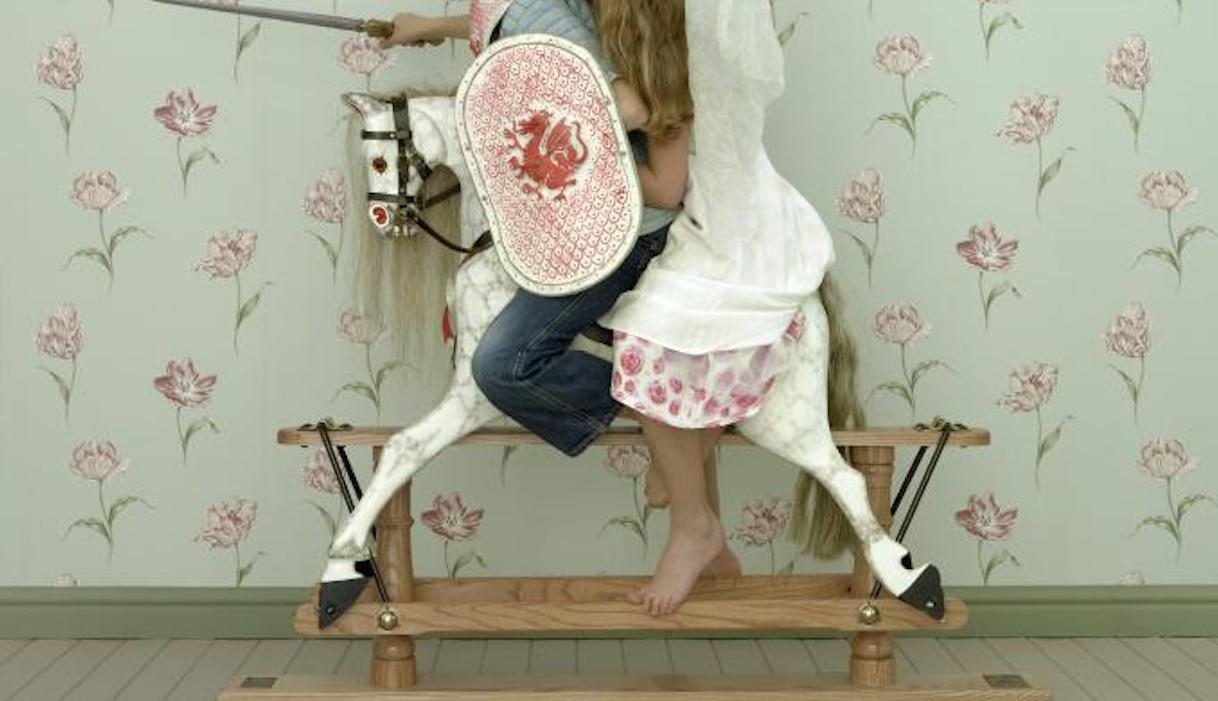 Deux enfants sur un cheval de bois en déguisement stéréotypés