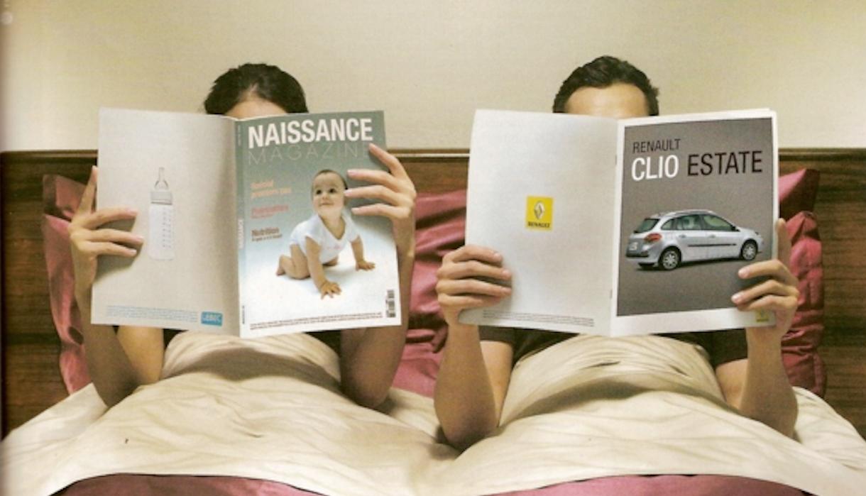 femme et homme lisant respectivement un magazine de naissance et un magazine de voiture dans un lit