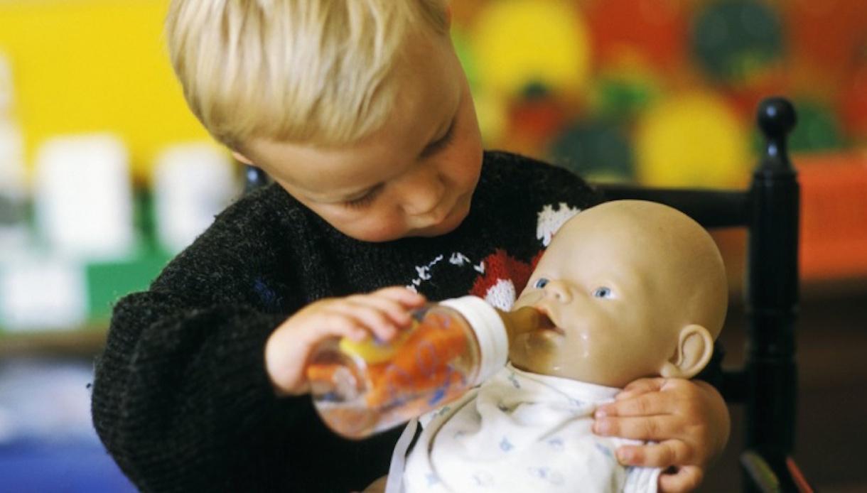 Petit garçon jouant avec un poupon