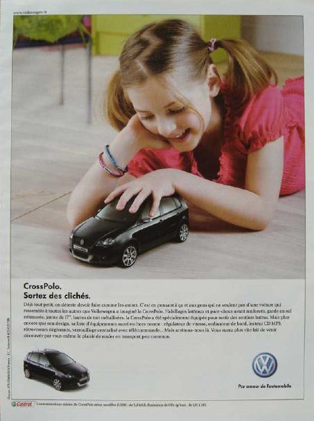 Une petite fille allongée sur le sol s'amuse avec une « petite » voiture
